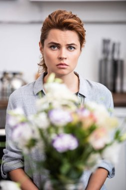 selective focus of upset woman looking at camera near flowers