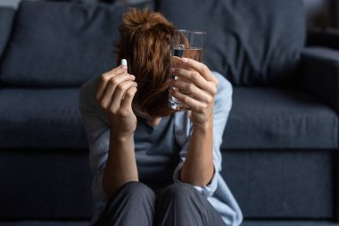 sick woman holding pill and glass of water at home