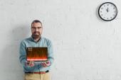Fotografie pohledný a usměvavý obchodník s notebookem na internetových stránkách obchodu