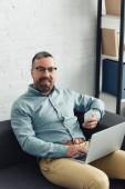 pohledný obchodník v košili držící laptop a smartphone v kanceláři