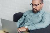 schöner Geschäftsmann in Hemd und Brille mit Laptop im Büro