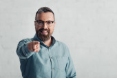 Fotografie handsome businessman in shirt pointing with finger and looking at camera