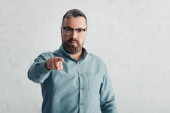 handsome businessman in shirt pointing with finger and looking at camera