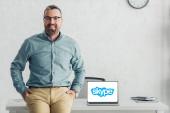 Kyiv, Ukrajna-augusztus 27, 2019: csinos üzletember ül asztal közelében laptop Skype logo