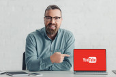 KYIV, UKRAINE - AUGUST 27, 2019: handsome businessman in shirt pointing with finger at laptop with youtube logo