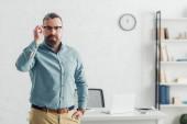 pohledný obchodník v košili a skleničkách, který se dívá na kameru v kanceláři