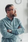bello uomo daffari in camicia e occhiali distogliere lo sguardo in ufficio