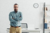 handsome businessman in shirt and glasses looking at camera in office