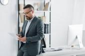 pohledný obchodník s formálním oblečením a brýlemi s použitím digitálního tabletu v kanceláři