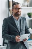 Fotografia bello uomo daffari in usura formale utilizzando tablet digitale in ufficio