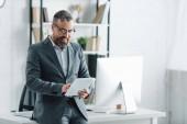 pohledný obchodník na formálním nošení pomocí digitálního tabletu v kanceláři