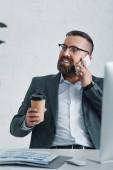 jóképű üzletember a formális kopás és szemüveg beszél a smartphone és a gazdaság papírpohár