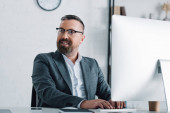 handsome businessman in formal wear and glasses using computer