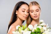 atraktivní blondýnka s asijskými bruneté ženy s květinami izolovanými na šedé
