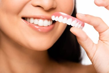 cropped view of woman holding false teeth isolated on white
