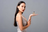 beautiful asian woman in elegant dress with red lips presenting perfume isolated on grey