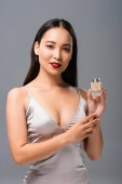 beautiful asian woman in elegant dress with red lips holding perfume isolated on grey