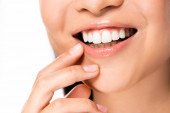 partial view of beautiful asian woman showing white teeth isolated on white