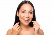smiling asian naked woman holding dental floss isolated on white