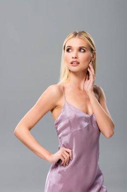 Elegant dreamy blonde girl in violet satin dress posing isolated on grey stock vector