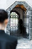 selektivní zaměření smutného staršího muže stojícího v budově u ženy na hřbitově