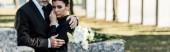 Fotografia panoramica colpo di anziano abbracciare donna al funerale