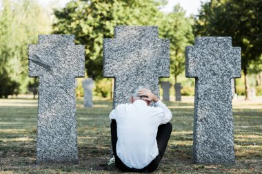 Back view of man with grey hair sitting near tombstones stock vector