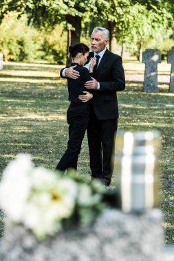 Selective focus of senior man hugging upset woman in cemetery stock vector