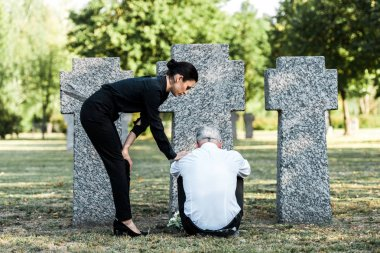 Beautiful woman standing near upset senior man sitting near tombs stock vector