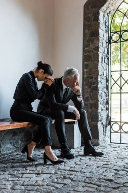 upset woman and sad man sitting on bench on funeral