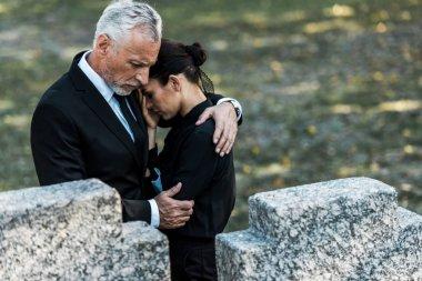 Selective focus of senior man hugging woman near tombs stock vector