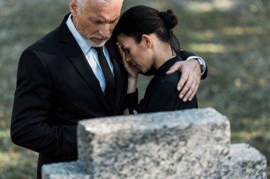 selective focus of senior man hugging upset woman near tombstone