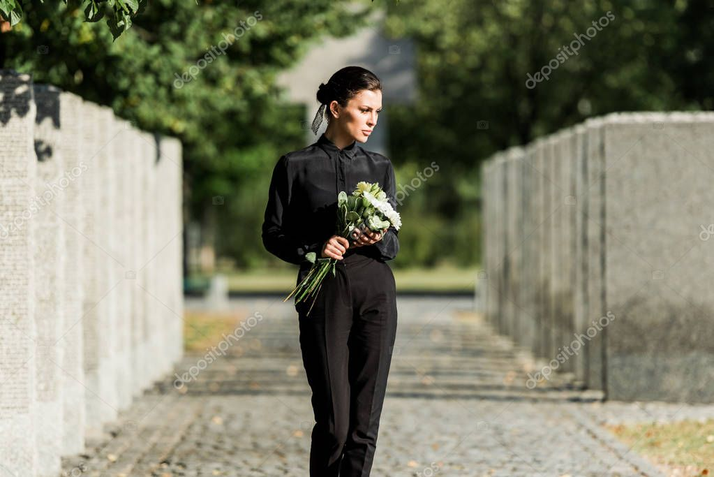 Sad woman holding white flowers and walking in graveyard stock vector