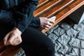 szelektív hangsúly a nő gazdaság zsebkendőjét ülve padon