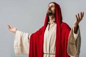 Szakállas férfi, vörös kapucnis, imádkozva kinyújtott kezekkel, szürke