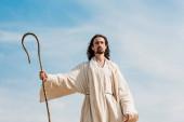 Jézus az ég és a felhők ellen a fa nádat tartja