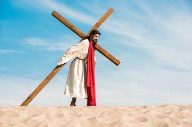 Jesus in wreath walking with cross in desert stock vector
