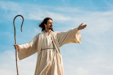 mavi gökyüzüne karşı ahşap baston tutan uzanmış el ile İsa