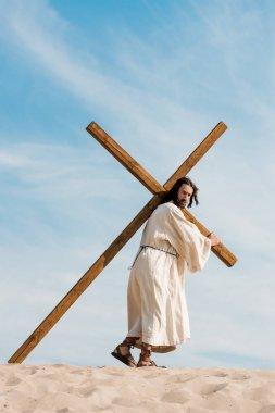jesus walking with wooden cross in desert