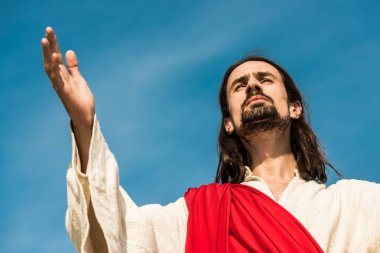 low angle view of man with outstretched hand against blue sky