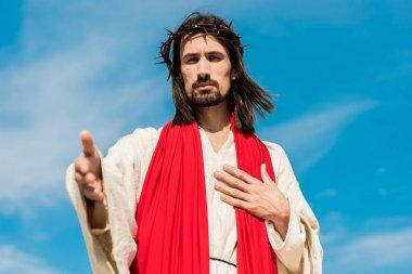 Selective focus of jesus in wreath gesturing against blue sky stock vector