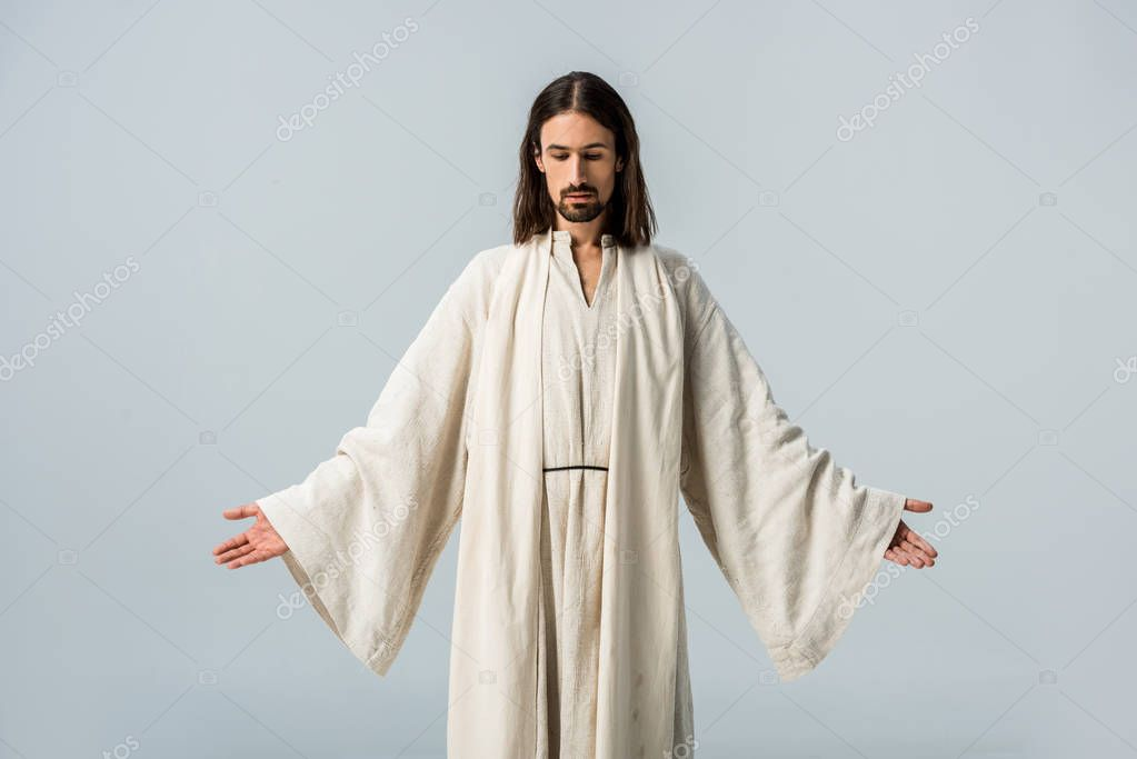 Man in jesus robe standing with outstretched hands isolated on grey
