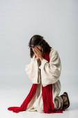Ježíš ve věnec zakrývající tvář při modlitbě na kolenou na šedé