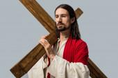hezký vousatý muž v Ježíšově róbě s dřevěným křížem izolovaným na šedé