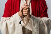 oříznutý pohled Ježíše držící růženec izolovaný na šedé
