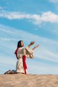 ember imádkozott térdre kinyújtott kezet a sivatagban a kék ég
