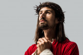 pohledný vousatý muž na věnce modlící se na šedé