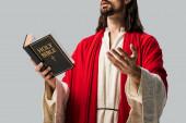 oříznutý pohled náboženského muže v Ježíšově rouchu, který má svatou Bibli a gestikuloval izolovaný na šedé