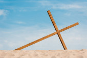Photo wooden cross on wavy and golden sand in desert