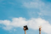 Photo cropped view of man holding holy bible and cross against blue sky with clouds